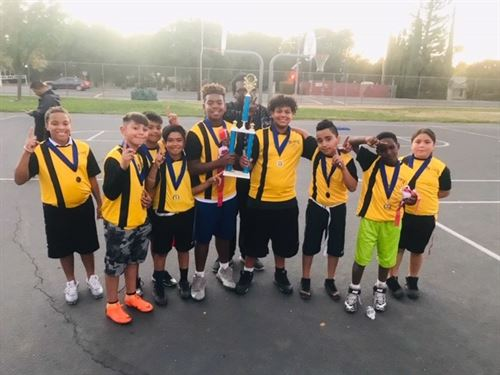 flag football team picture on playground with trophy